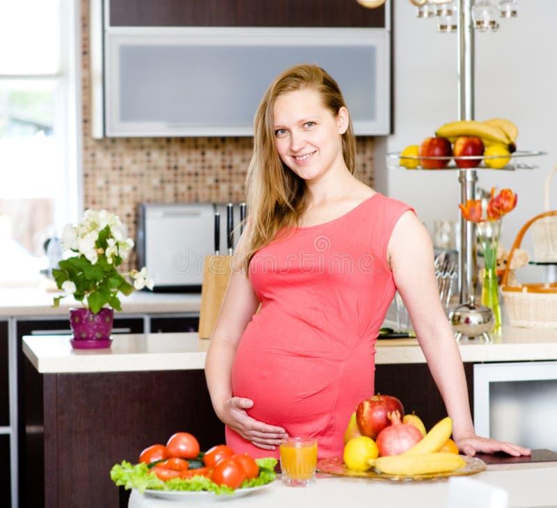 Retrato de la mujer embarazada hermosa que sostiene el vientre en kitchen fotos de archivo libres de regalías
