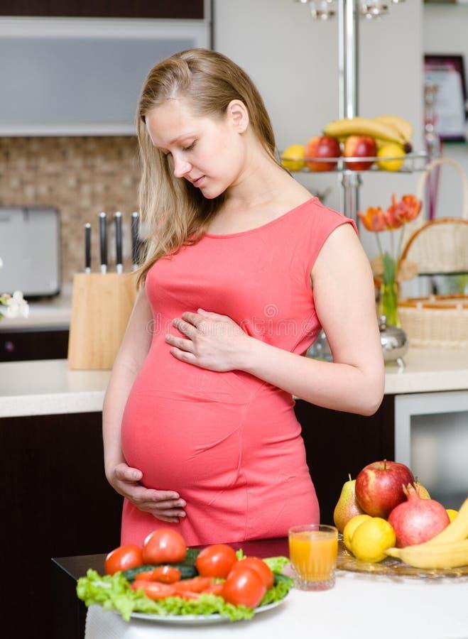 Retrato de la mujer embarazada hermosa que sostiene el vientre en kitchen foto de archivo