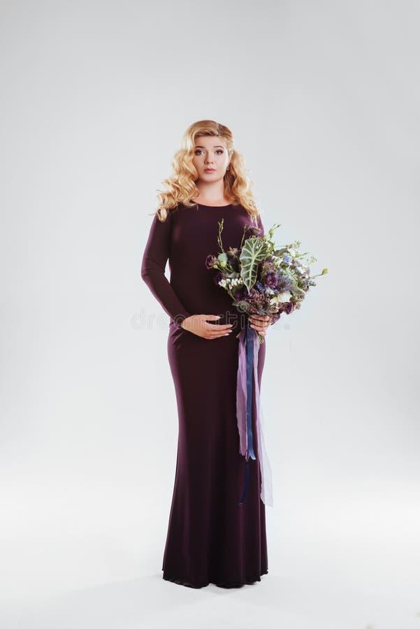 Retrato de la mujer embarazada joven con la flor grande en su mano imagen de archivo libre de regalías