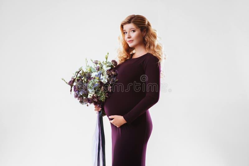 Retrato de la mujer embarazada joven con la flor grande en su mano foto de archivo libre de regalías