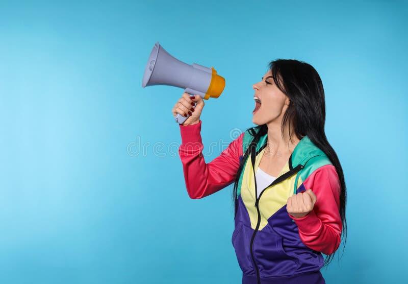 Retrato de la mujer emocional que usa el megáfono en fondo del color fotos de archivo libres de regalías