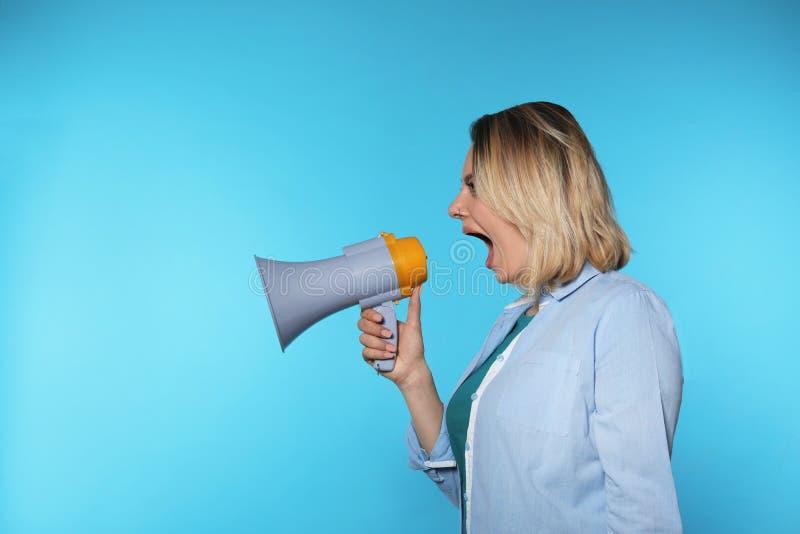 Retrato de la mujer emocional que usa el megáfono en fondo del color fotos de archivo
