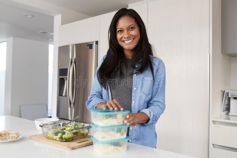 Retrato de la mujer en la cocina que prepara la comida de alto valor proteico y que pone porciones en los envases fotos de archivo
