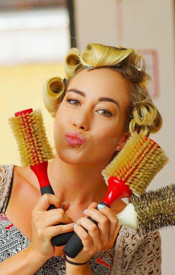 Retrato de la mujer en el peluquero, sosteniendo en sus manos muchos cepillos de la ronda, en un salón de pelo foto de archivo