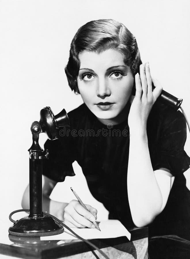 Retrato de la mujer en el teléfono que toma notas (todas las personas representadas no son vivas más largo y ningún estado existe imagenes de archivo