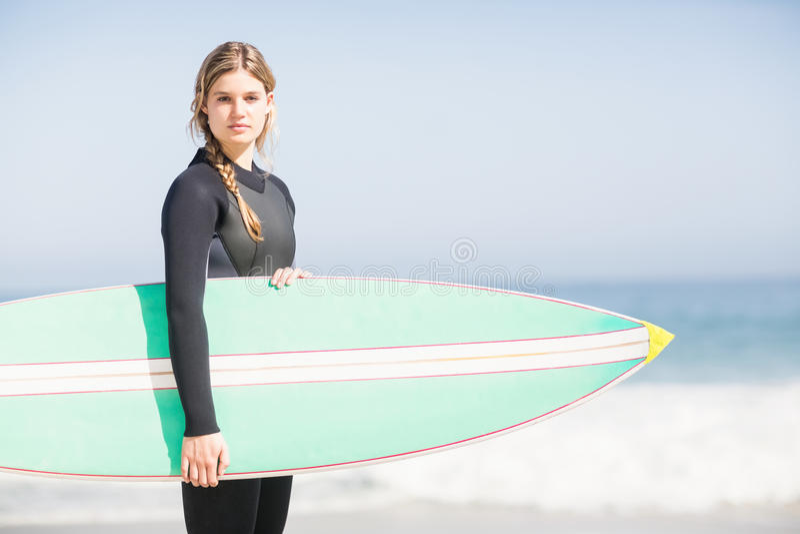 Retrato de la mujer en el wetsuit que sostiene una tabla hawaiana en la playa fotografía de archivo