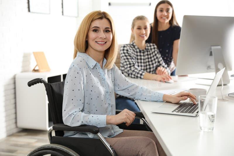 Retrato de la mujer en silla de ruedas con sus colegas imagen de archivo