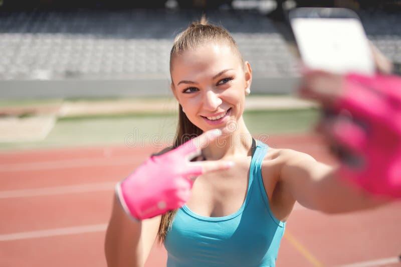 Retrato de la mujer encantadora que toma un selfie, una imagen de sí misma durante el entrenamiento Entrenamiento, aptitud y tecn imagen de archivo