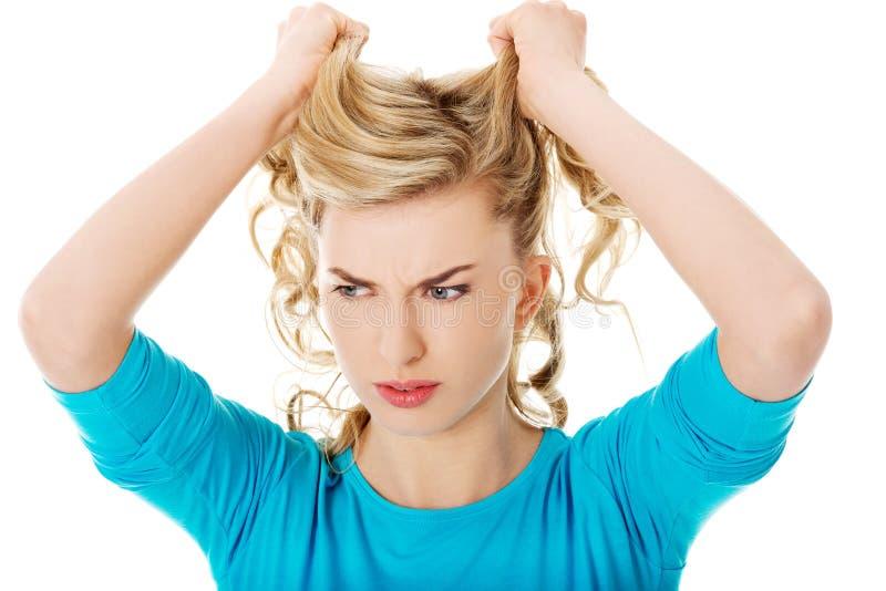Retrato de la mujer enojada que tira de su pelo foto de archivo