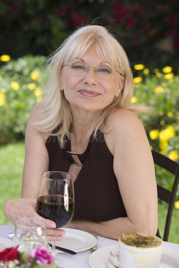 Retrato de la mujer envejecida centro con el vino rojo al aire libre foto de archivo libre de regalías