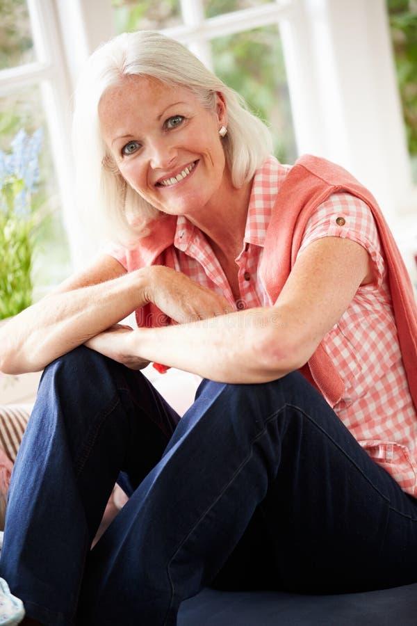 Retrato de la mujer envejecida centro que se sienta en la ventana Seat fotografía de archivo