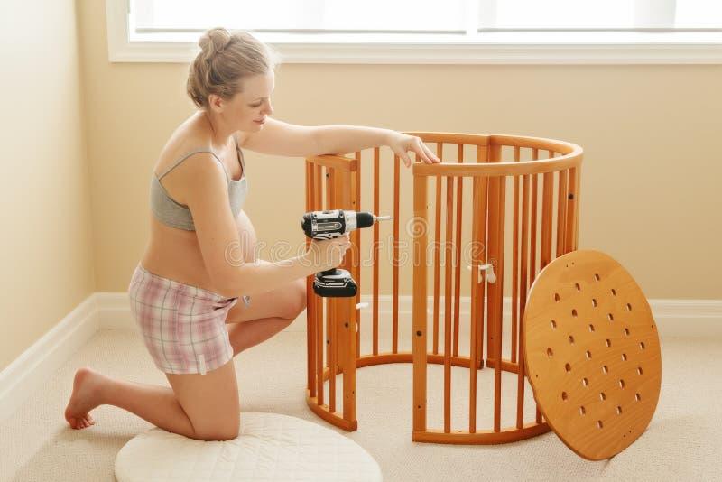 Retrato de la mujer feliz caucásica blanca joven que monta el pesebre de madera del bebé en cuarto de niños en casa imagen de archivo libre de regalías
