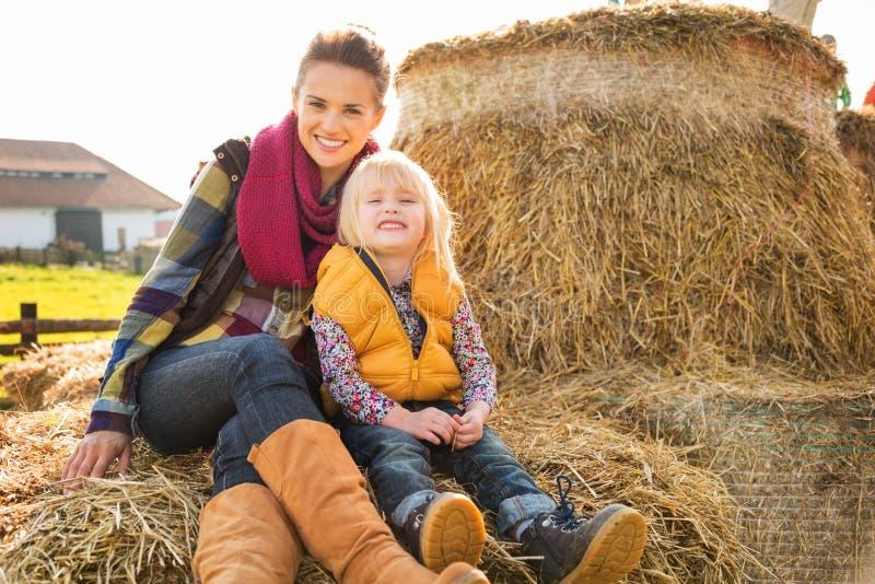Retrato de la mujer feliz con el niño lindo que se sienta en el heno en granja imagenes de archivo