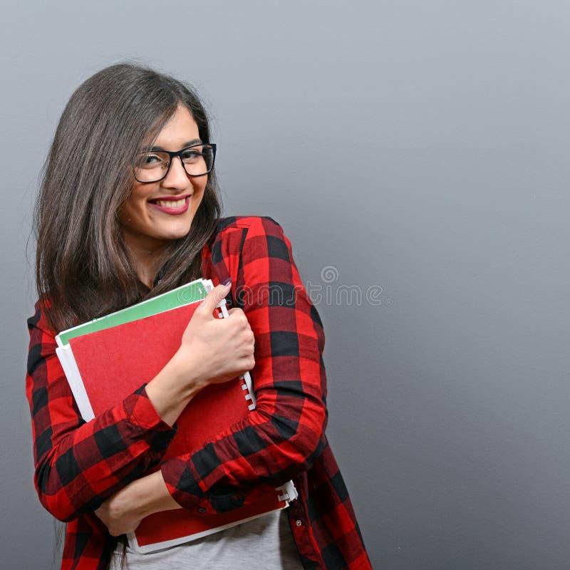 Retrato de la mujer feliz del estudiante que sostiene los libros contra fondo gris foto de archivo
