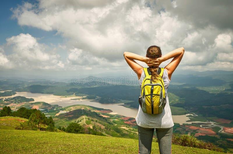 Retrato de la mujer feliz del viajero con la mochila que se coloca en el top o imagen de archivo libre de regalías