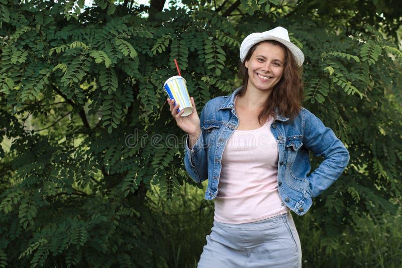 Retrato de la mujer feliz joven con el cóctel foto de archivo