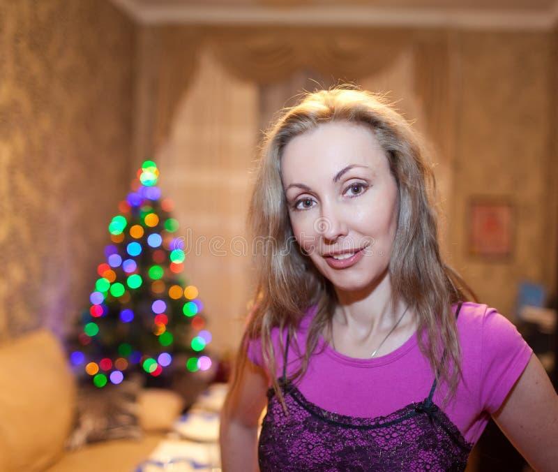 Retrato de la mujer feliz joven contra un árbol del Año Nuevo foto de archivo