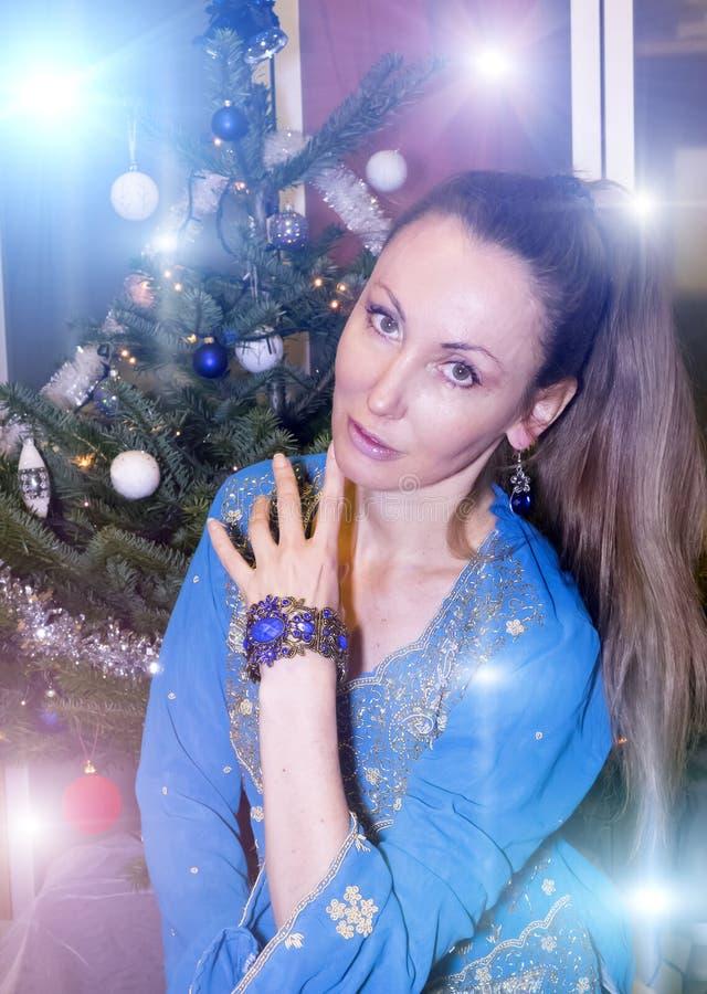Retrato de la mujer feliz joven contra un árbol del ` s del Año Nuevo imagenes de archivo