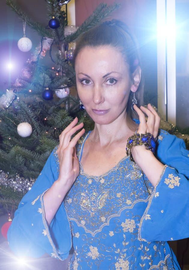 Retrato de la mujer feliz joven contra un árbol del ` s del Año Nuevo fotos de archivo libres de regalías