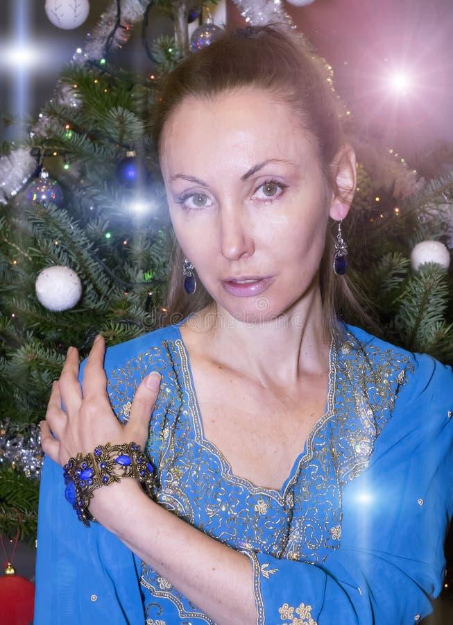 Retrato de la mujer feliz joven contra un árbol del ` s del Año Nuevo foto de archivo