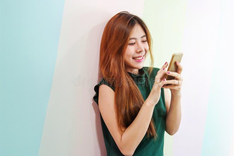 Retrato de la mujer feliz joven, femenino usando un teléfono elegante imagenes de archivo
