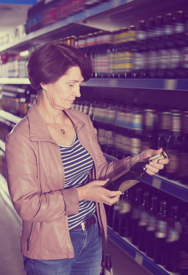 Retrato de la mujer feliz que compra una cerveza imagen de archivo