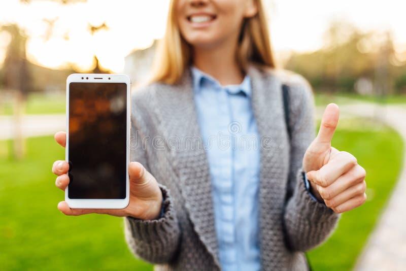 Retrato de la mujer feliz que muestra la pantalla en blanco del teléfono móvil, y s fotografía de archivo