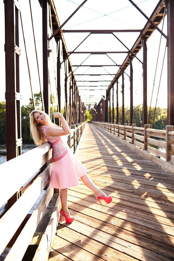 Retrato de la mujer feliz que presenta en el puente de madera foto de archivo libre de regalías