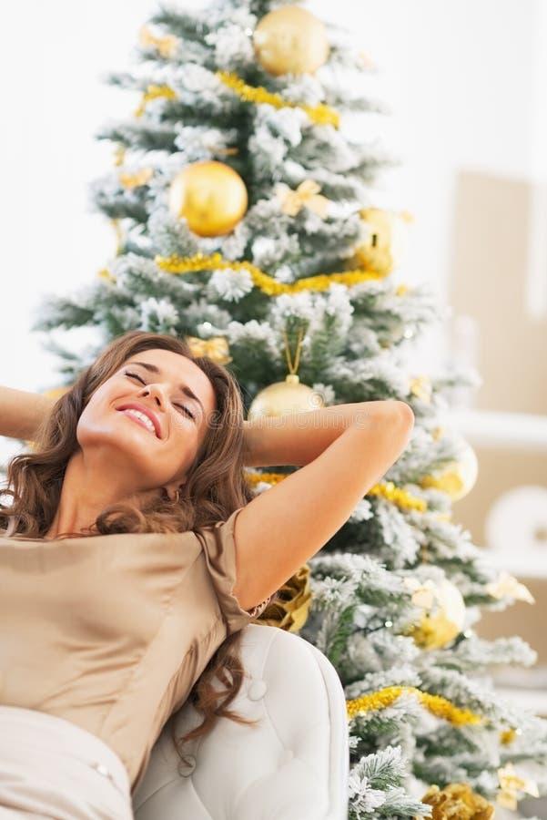 Retrato de la mujer feliz que se relaja delante del árbol de navidad foto de archivo