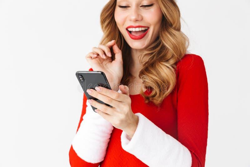 Retrato de la mujer feliz 20s que lleva el traje rojo de Santa Claus que sonríe y que sostiene smartphone negro, aislado sobre el foto de archivo