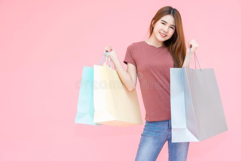 Retrato de la mujer feliz sonriente joven hermosa que lleva a cabo el fondo rosado aislado de los bolsos de compras imagenes de archivo