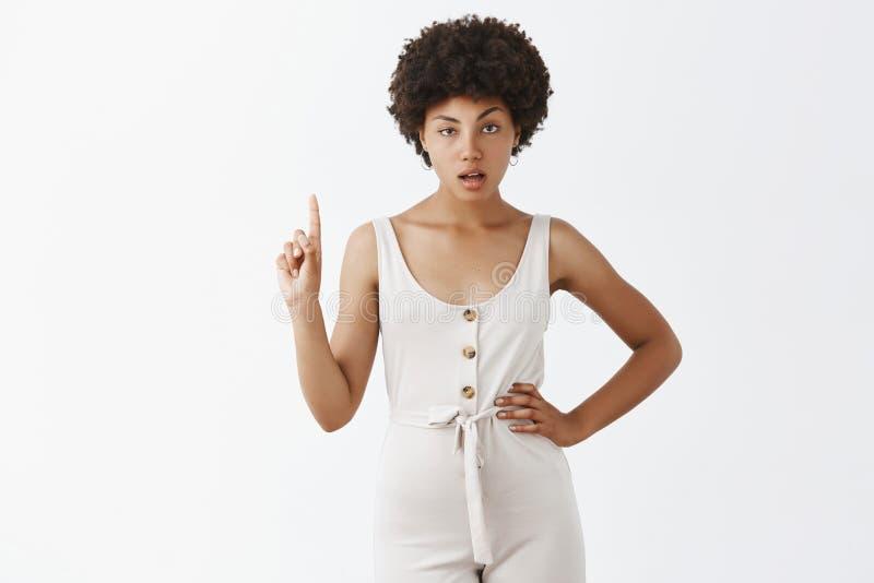 Retrato de la mujer femenina elegante afroamericana de serio-mirada con la mano de la tenencia del pelo rizado en la cintura y ag fotografía de archivo libre de regalías
