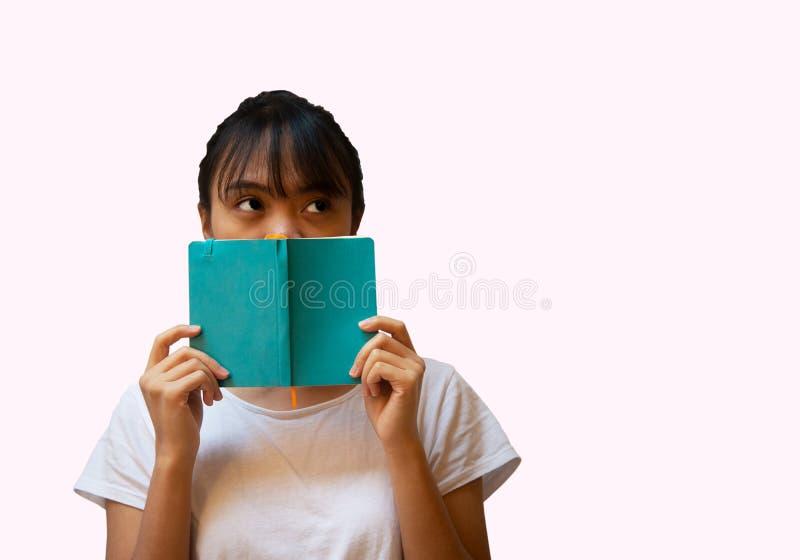 retrato de la mujer de Filipinas del asiático 20s con la cara azul de la cubierta del cuaderno para el fondo rosado de la educaci imagen de archivo