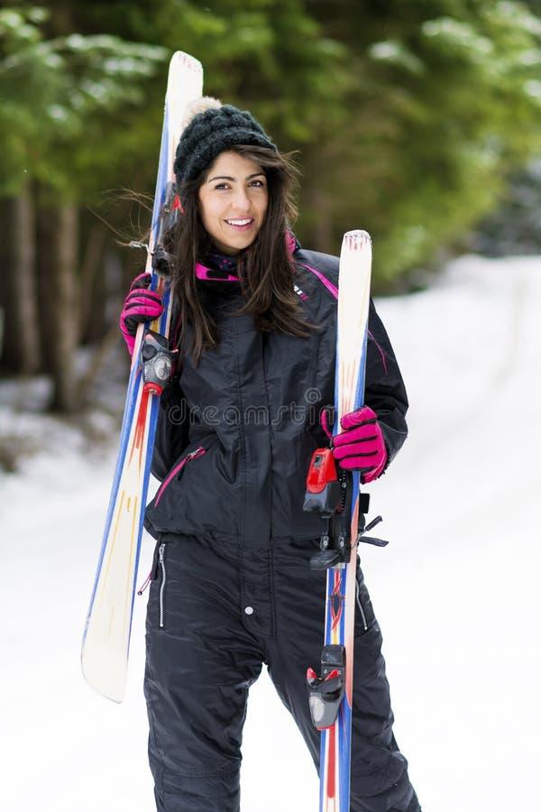 Retrato de la mujer hermosa con el esquí y el traje de esquí en montaña del invierno imagenes de archivo