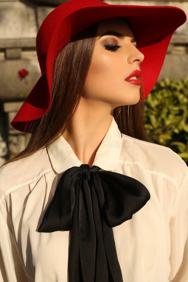 Retrato de la mujer hermosa con el pelo oscuro en sombrero rojo elegante imágenes de archivo libres de regalías