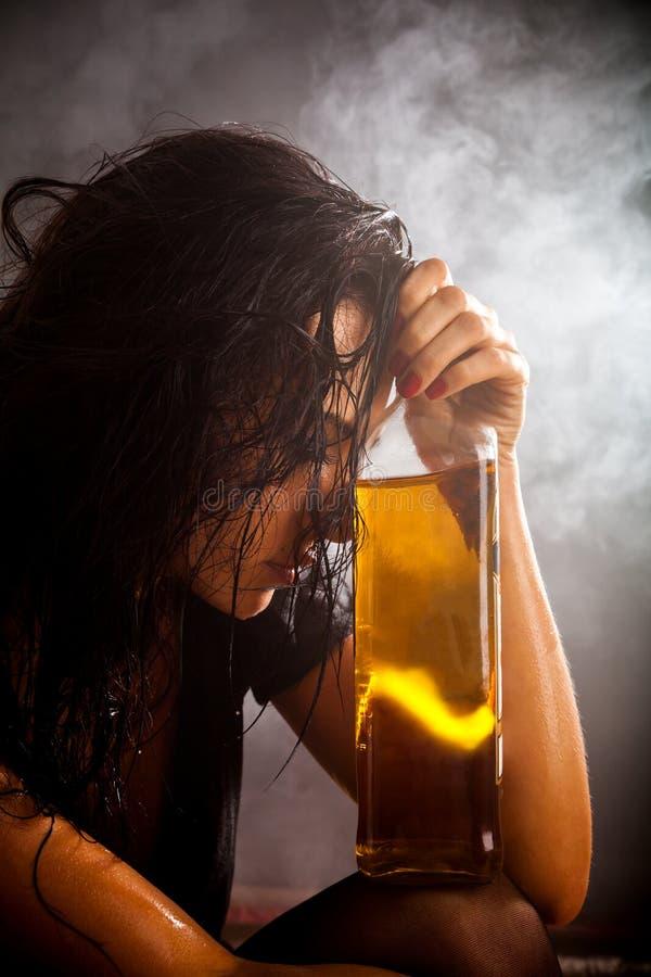 Retrato de la mujer hermosa con la botella de bebida del alcohol foto de archivo