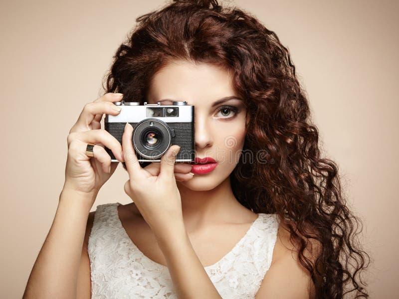 Retrato de la mujer hermosa con la cámara. Fotógrafo de la muchacha foto de archivo libre de regalías
