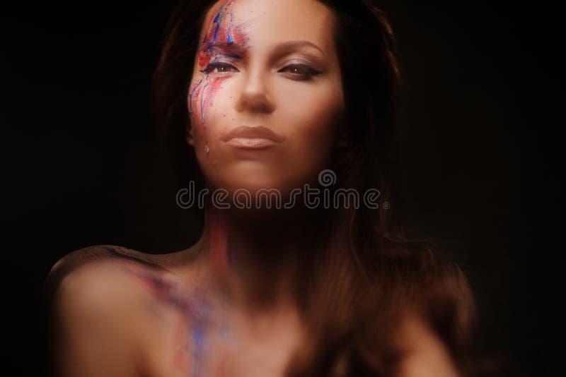 Retrato de la mujer hermosa con maquillaje coloreado creativo en un fondo oscuro imagen de archivo
