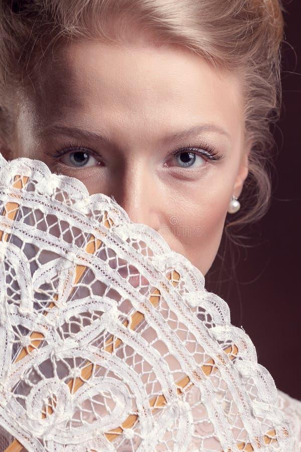 Retrato de la mujer hermosa con una fan oriental en su cara fotos de archivo libres de regalías