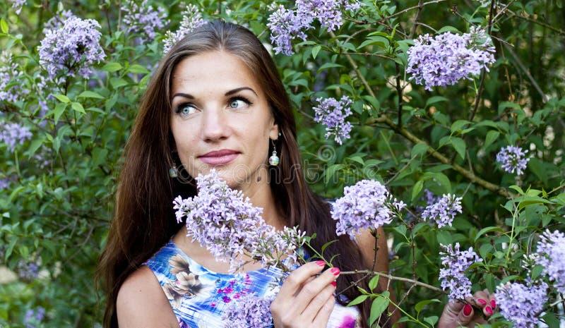 Retrato de la mujer hermosa del brunnete entre las flores púrpuras imágenes de archivo libres de regalías