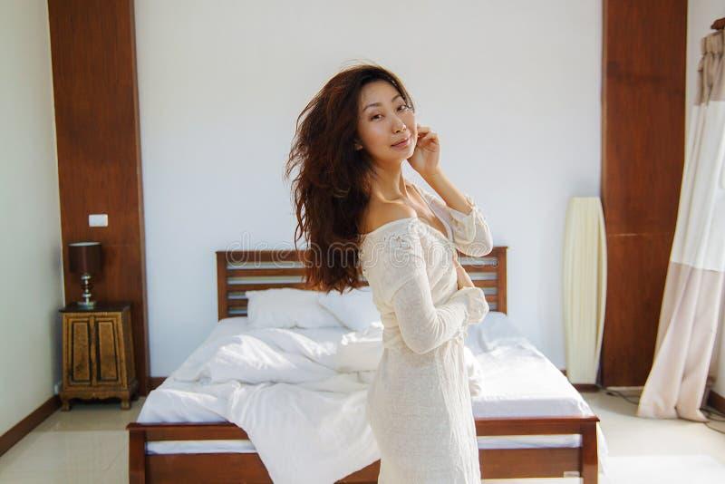 Retrato de la mujer hermosa en cama en el dormitorio imagen de archivo