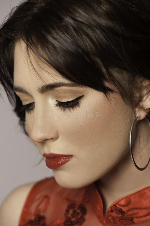 Retrato de la mujer hermosa en el rojo que mira abajo fotos de archivo libres de regalías