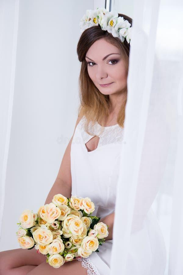 Retrato de la mujer hermosa en el vestido blanco con las flores cerca del foto de archivo libre de regalías