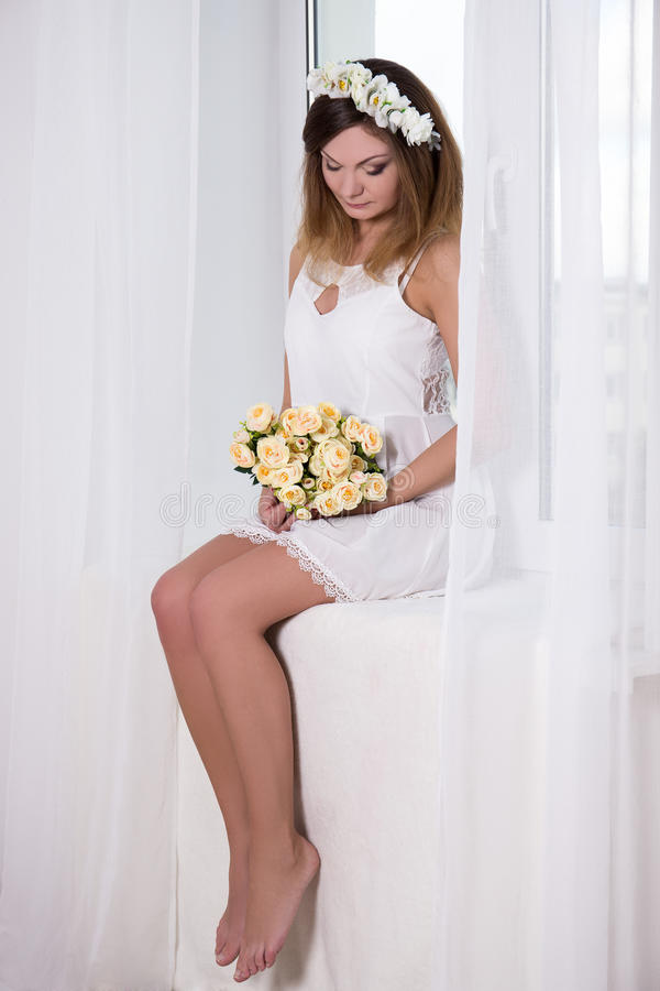 Retrato de la mujer hermosa en el vestido blanco con sentarse de las flores fotografía de archivo
