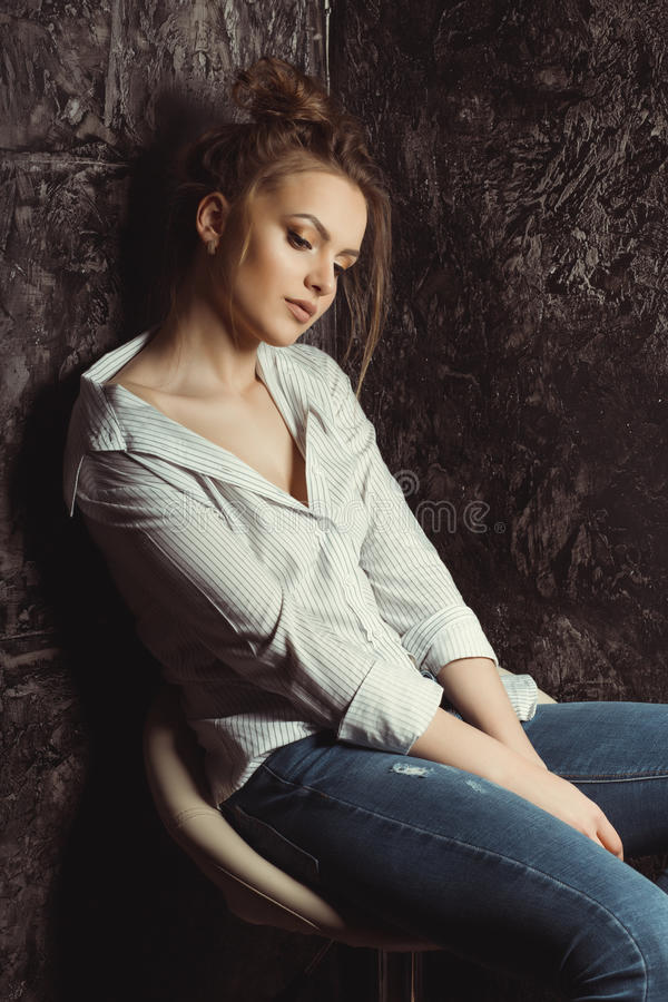 Retrato de la mujer hermosa en la camisa que se sienta en una silla fotografía de archivo libre de regalías