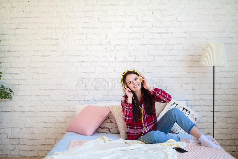 Retrato de la mujer hermosa en la música que escucha de la mañana que se sienta en cama en casa fotos de archivo