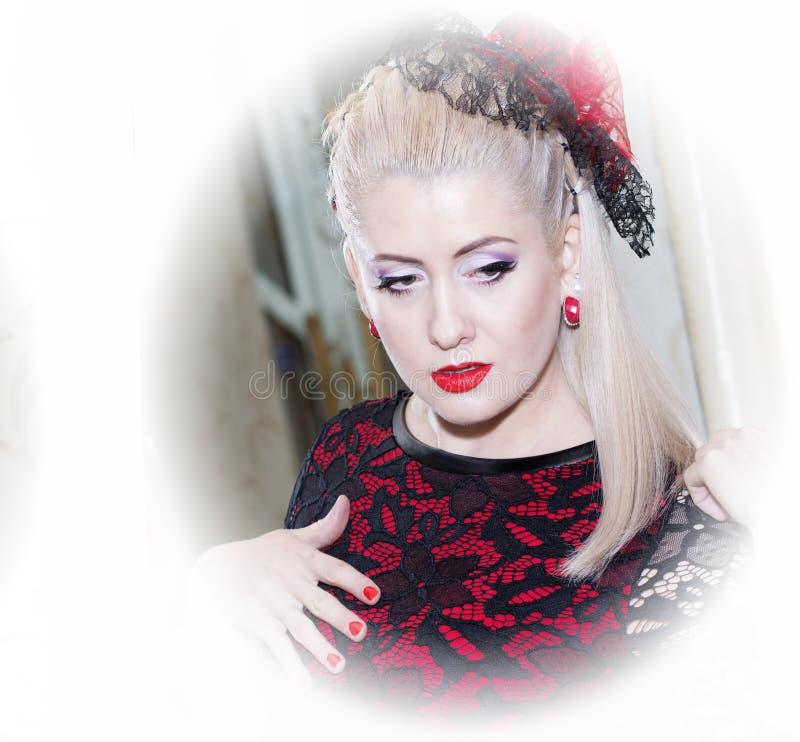 Retrato de la mujer hermosa en un vestido rojo y un sombrero foto de archivo