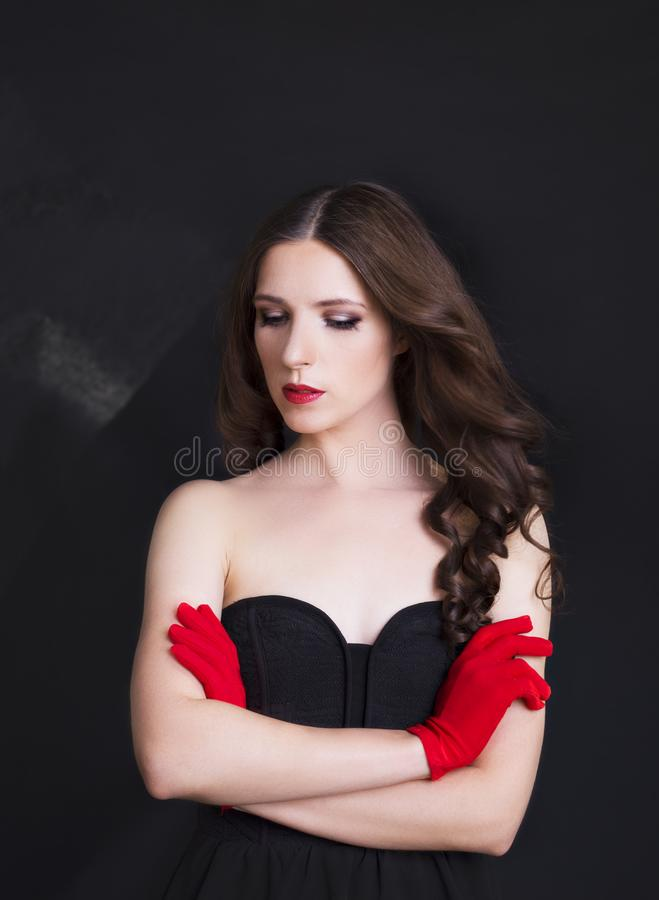 Retrato de la mujer hermosa en vestido negro con el pelo rizado - aislado en fondo negro imagen de archivo libre de regalías