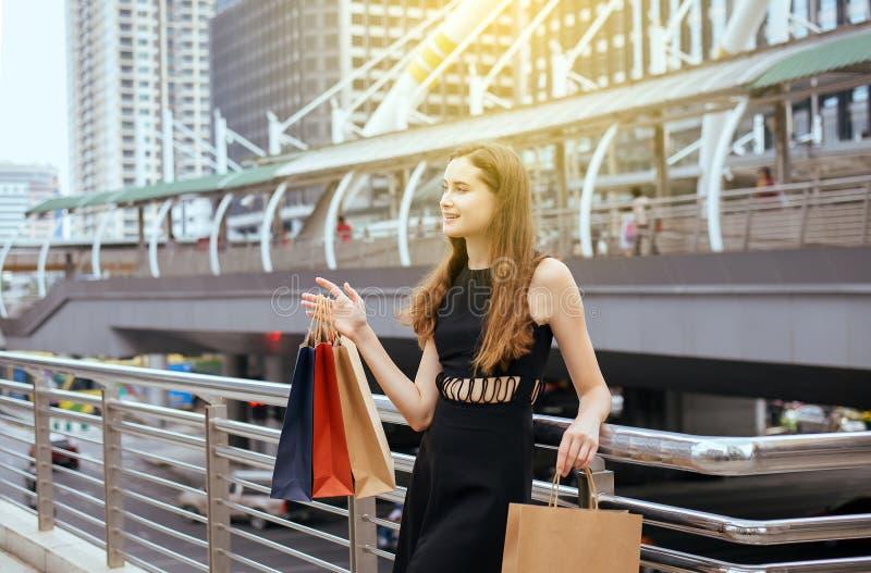 Retrato de la mujer hermosa en vestido negro que sonríe y que sostiene la ciudad de los bolsos de compras en el centro, concepto  foto de archivo libre de regalías