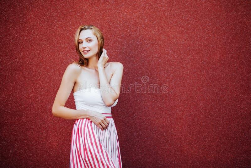 Retrato de la mujer hermosa en vestido rojo, sonriendo imagenes de archivo